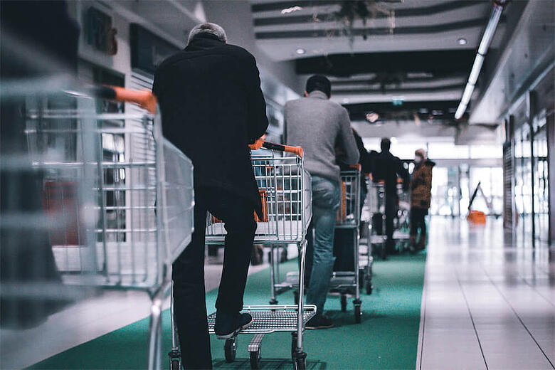 Shoppers with trolleys waiting in line